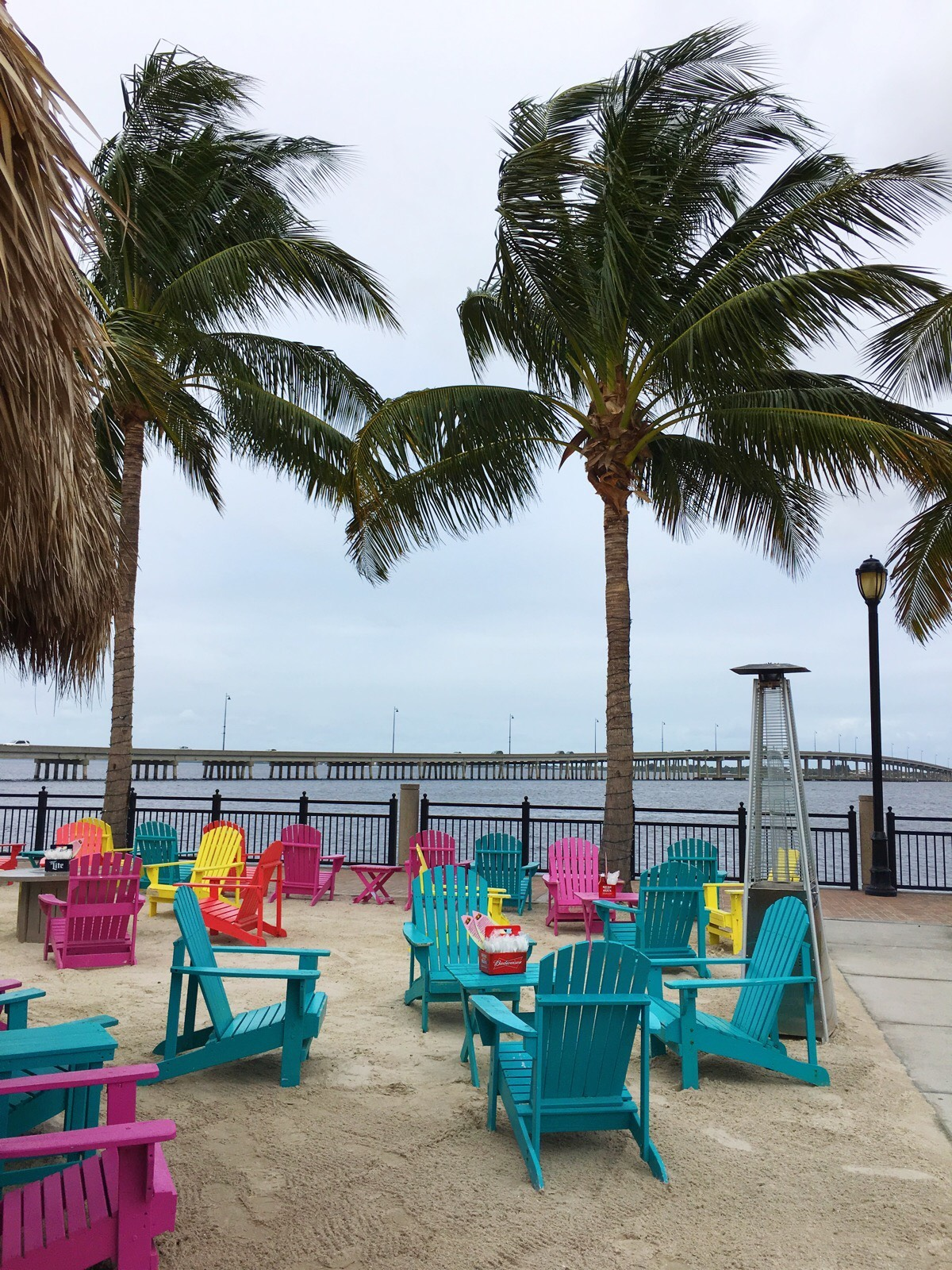 This photo depicts Punta Gorda, and all the palm trees and different colored chairs outside by the beach bar.