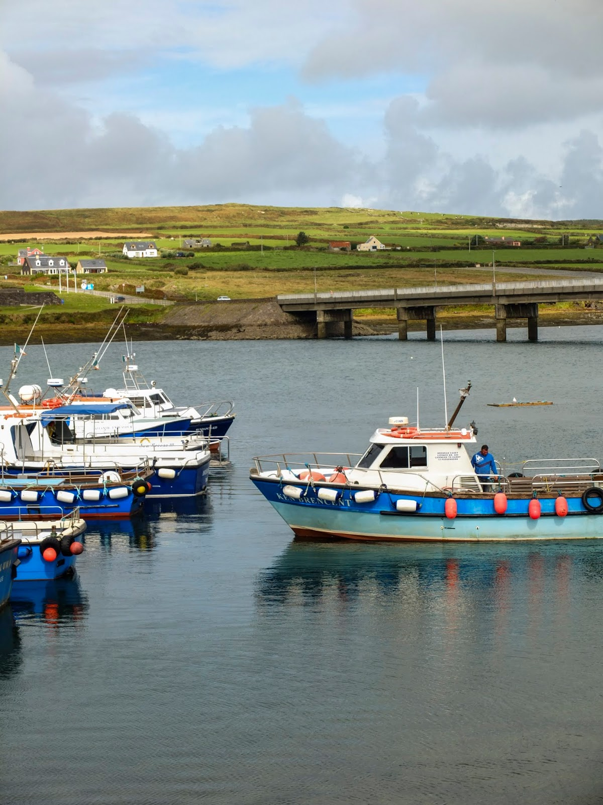 Sun shining on blue and white boats moored in Portmagee, Co.Kerry