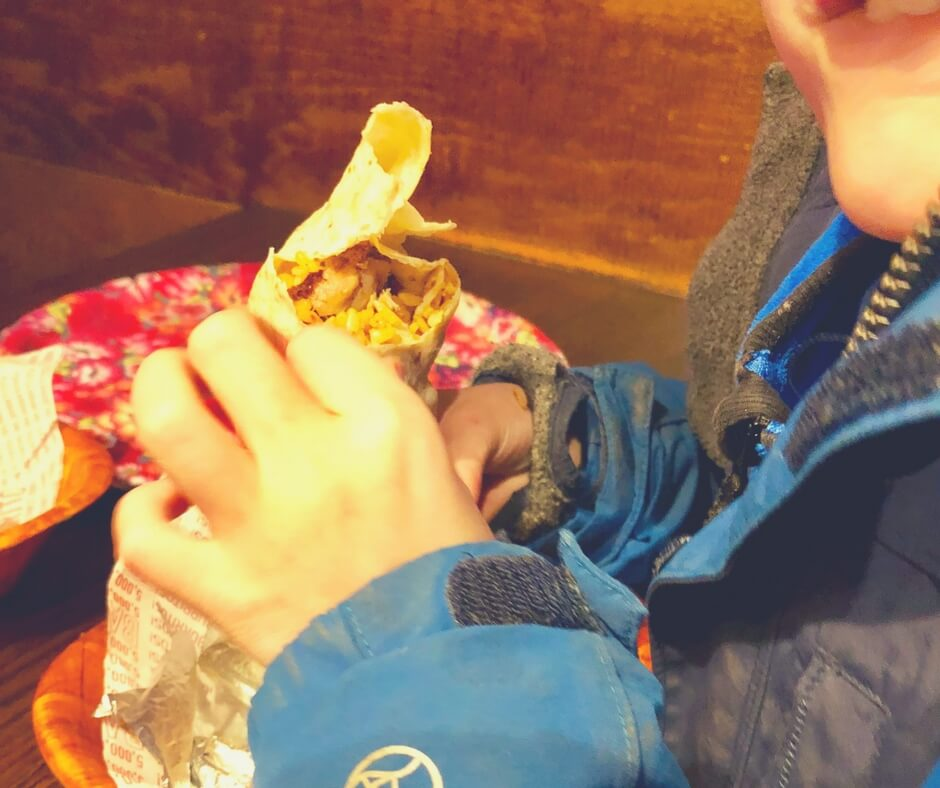 A regular burrito with brown rice and grilled chicken from Barburrito, Nottingham. A young boy is eating it with a huge smile on his face.