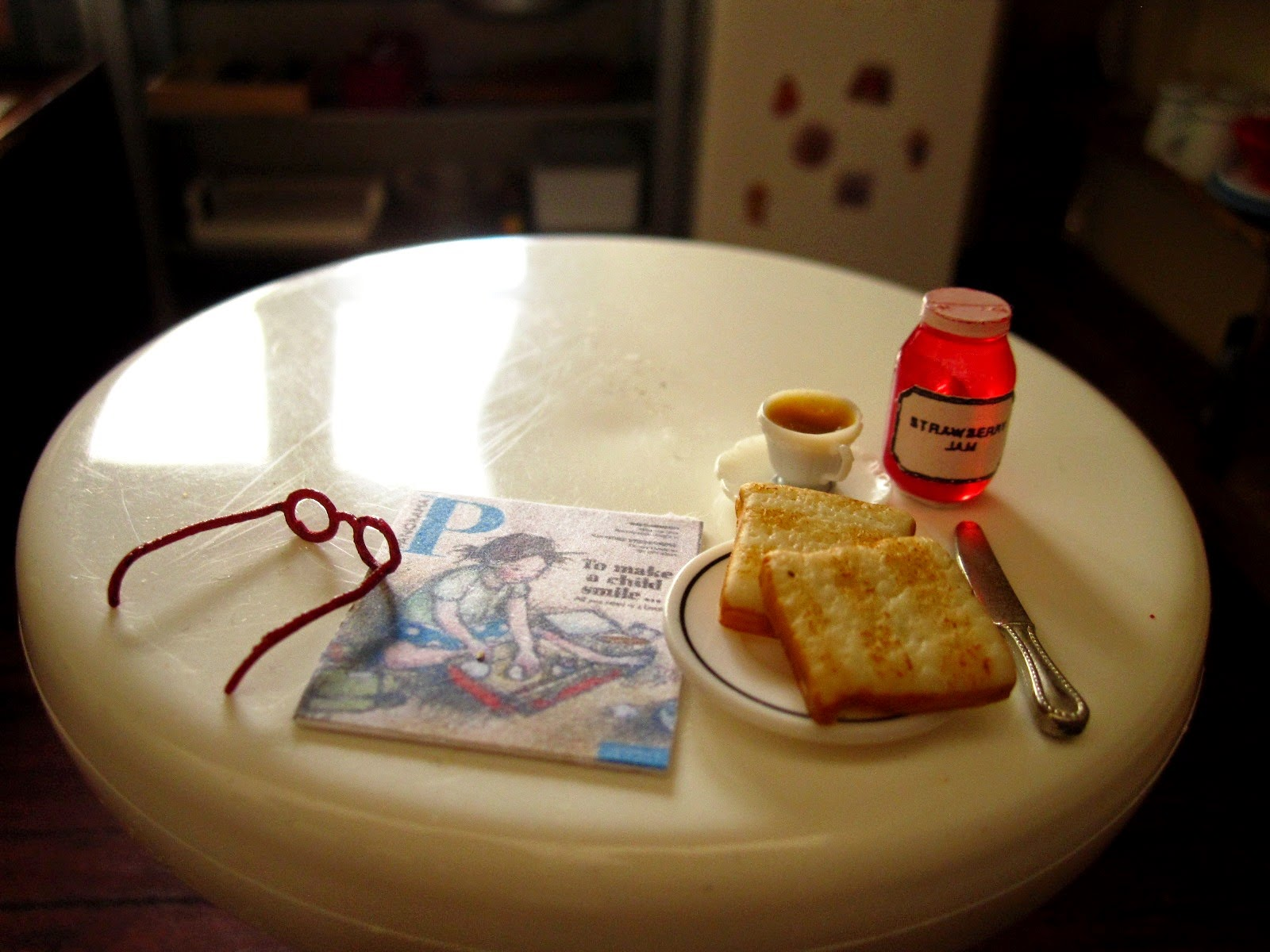 Modern miniature round kitchen table with reading glasses and magazine plus tea, toast and jam.