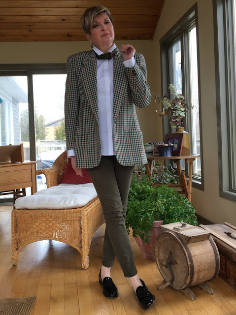 woman in checked jacket, white blouse, khaki jeans, and loafers