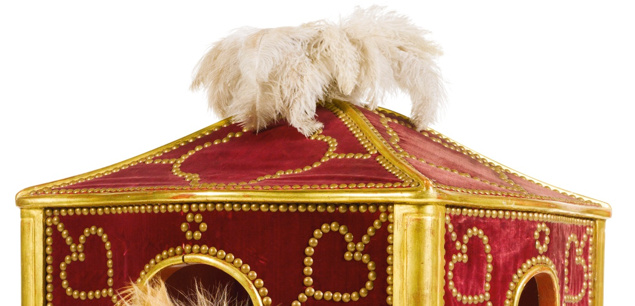 the 18th century sedan dog chair has feathers at the top and a heart motif along the walls.
