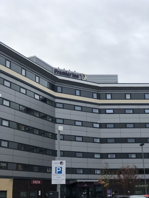The front of the Premier Inn at Manchester Airport. The building is grey against a cloudy sky
