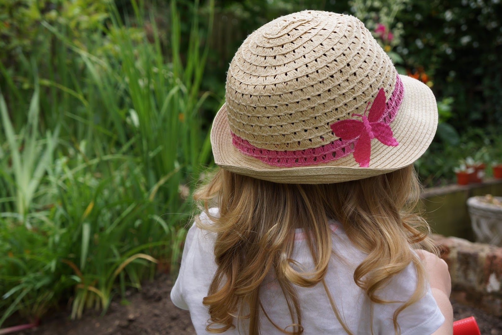 straw hat with a pink woven butterfly on it