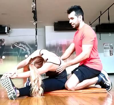 Ejercicio en parejas para estirar los músculos isquiotibiales y oblicuos