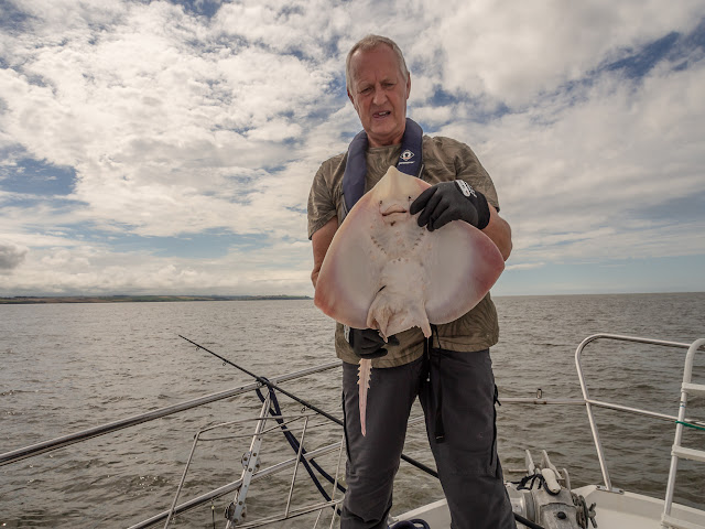 Photo of Phil with the biggest ray he caught that day on the broken rod behind him