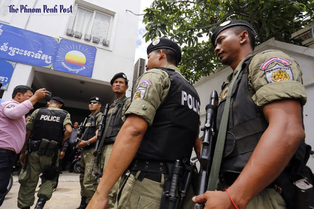 Heavily armed police wait in front of the CNRP headquarters in Phnom Penh during a search for acting opposition leader Kem Sokha yesterday. Pha Lina