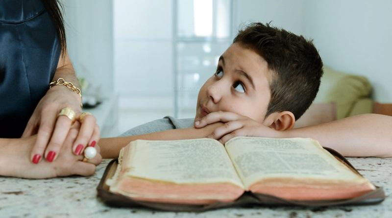 Menino olha sua mães que o ensina sobre a Bíblia sagrada sobre a mesa