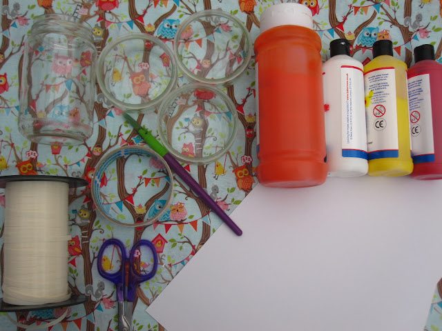 Craft supplies, including paint, glass jars, card, ribbon, tape, scissors and a paintbrush