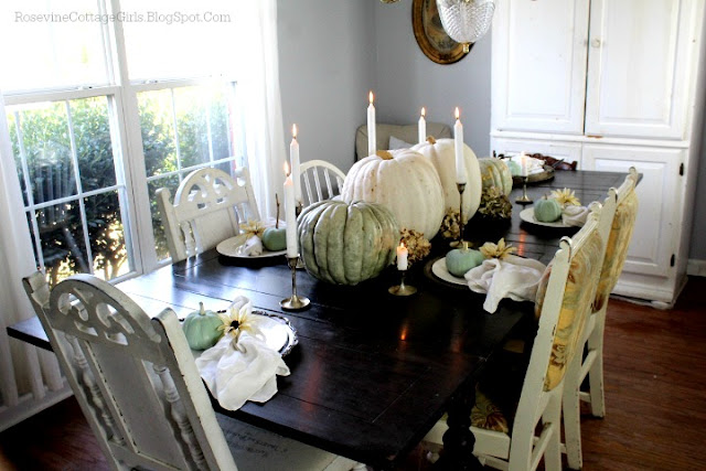 Green mottled pumpkin and large white pumpkins down the middle of a black table with lit candles for thanksgiving | rosevinecottagegirls.com
