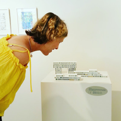Woman looking at small porcelain buildings in a gallery.