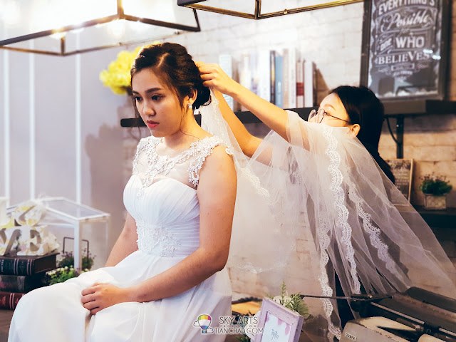 Putting on a long wedding veil to add on that special feel