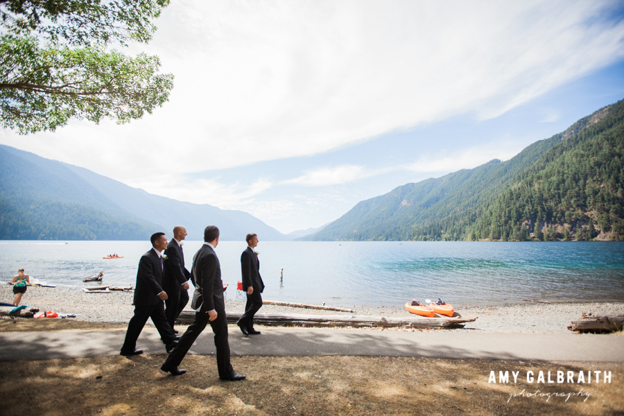 groomsmen walking together on the beach of a scenic lake