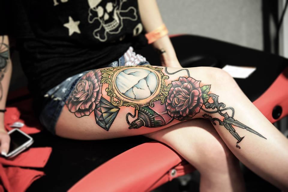 Chica sentada con piernas cruzadas y un tatuaje de espejo con diamante y rosas