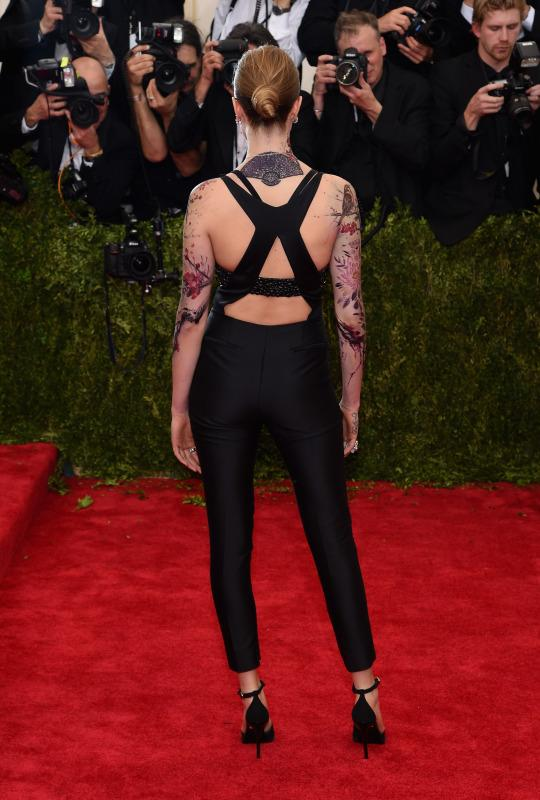 Cara Delevingne pairs plunging jumpsuit with oriental tattoos at the 2015 Met Gala in NYC