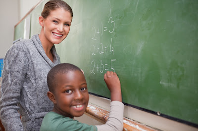 image of a teacher with a student at a blackboard