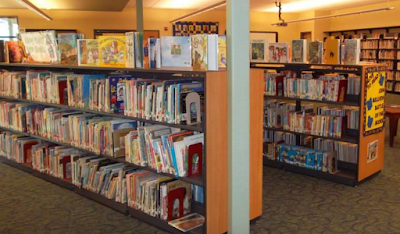Children's books arranged on library shelves and counter-top displays
