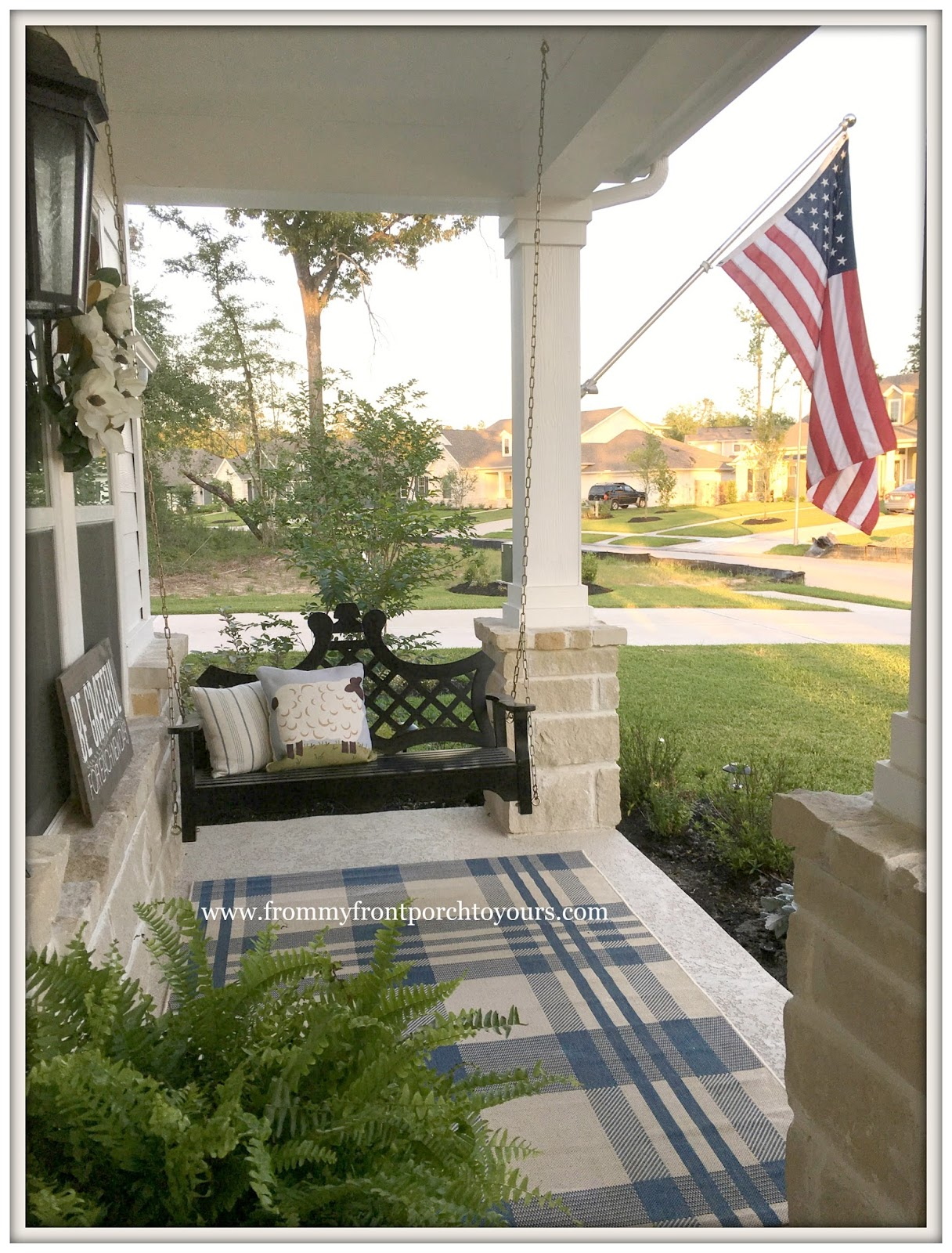 Suburban farmhouse front porch porch swing plaid outdoor rug american flag from