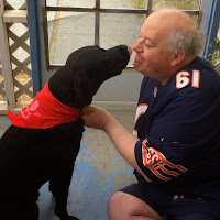 William and Leif sit facing each other, Leif wears a red bandana and leans forward and looks as if about to kiss William who is on the right kneeling wearing a Chicago Bears Shirt.