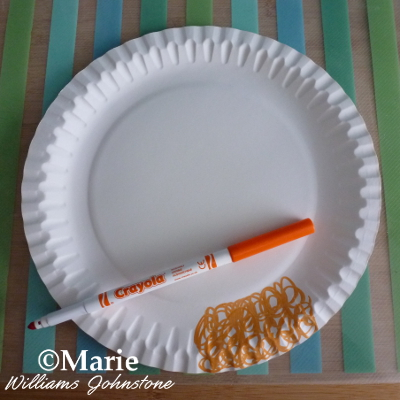 White paper plate with orange marker pen