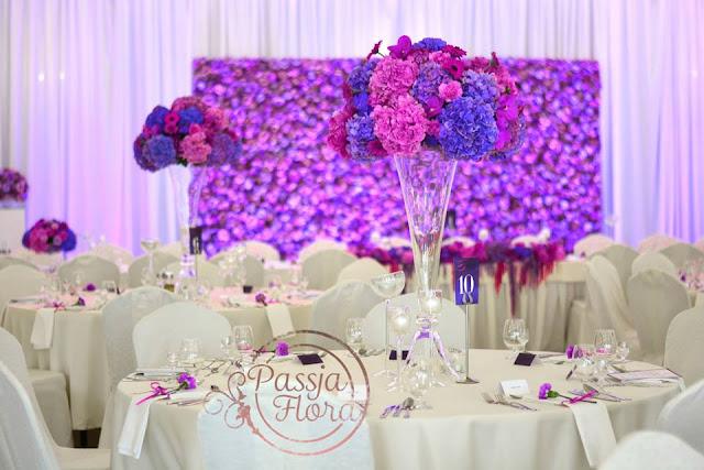 Fioletowe kwiaty na sali weselnej