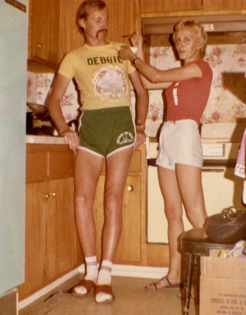1970s Dads - the original hipsters. Dad in the kitchen wearing socks and sandals and a Debbie shirt. The New Dad. marchmatron.com