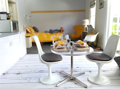 One-twelfth scale modern miniature motel room in white, grey and yellow.