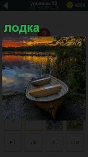 В свете вечернего заката на берегу речки около кустов лежит лодка