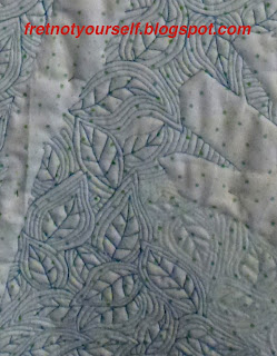 Intricate, small leaves are stitched in royal blue thread on the back of this quilt.