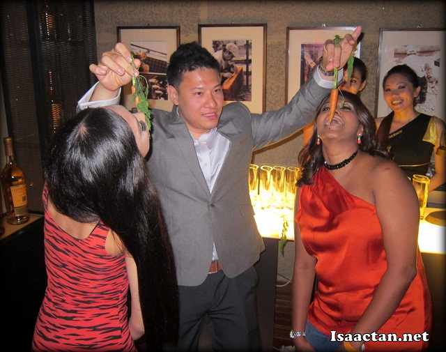 Two ladies eating some carrots off the hands of Michael Tan, Brand Manager for Glenmorangie