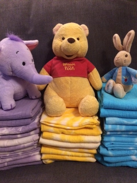 Piles of tie-dyed muslins in purple, yellow and blue with matching coloured soft toys on top