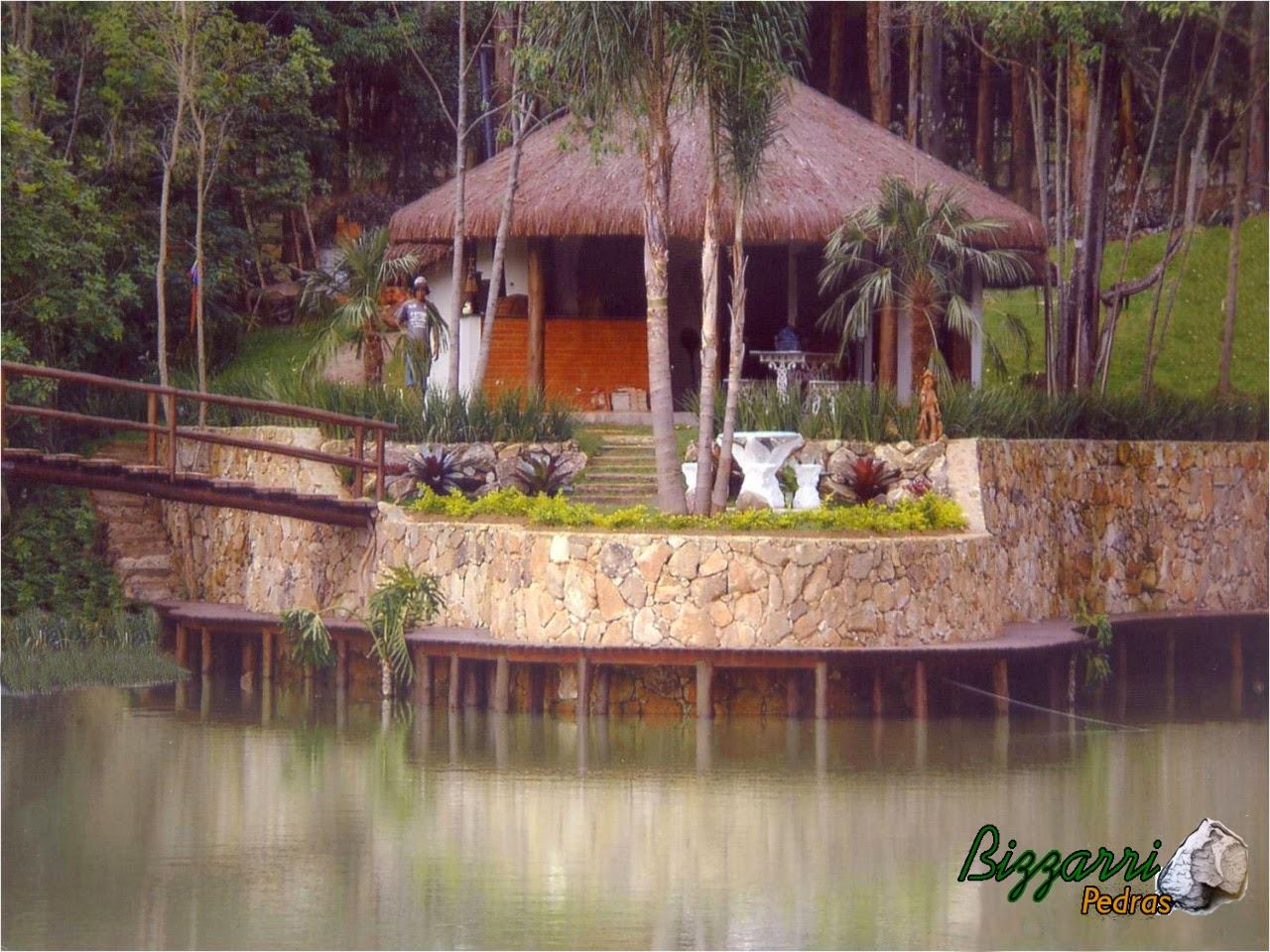 Detalhe na construção do lago o muro de pedra e o quiosque de piaçava com a construção da churrasqueira, a ponte de madeira e o deck de madeira para poder sentar e pescar.