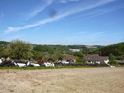 Ein kleines, beschauliches Dorf liegt vor einer schönen, bergigen Kulisse und tollem. blauen Himmel