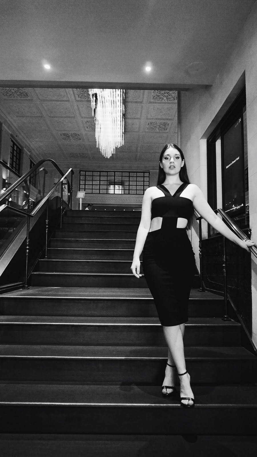 black and white photo of girl standing in Stewart Hotel NYC lobby