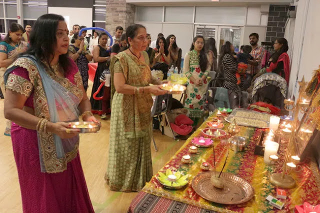 "Rashmika Patel and Radha ben Patel perform the ""arti"" traditional worship rituals as the local Indian community celebrated Diwali recently at Rotary Place."