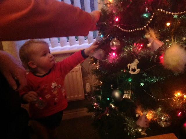 toddler and Christmas tree with adult arm in view