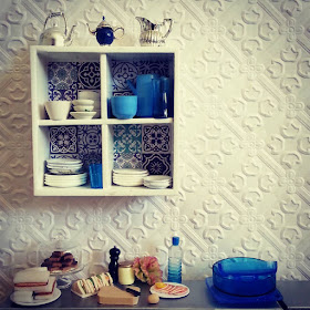 Modern miniature white wall shelf with blue and white tiles on the back, filled with blue and white crockery and with various jugs displayed on the top. Underneath, on a metal bench top, are the plates of cakes and sandwiches, with the sandwich components laid out.