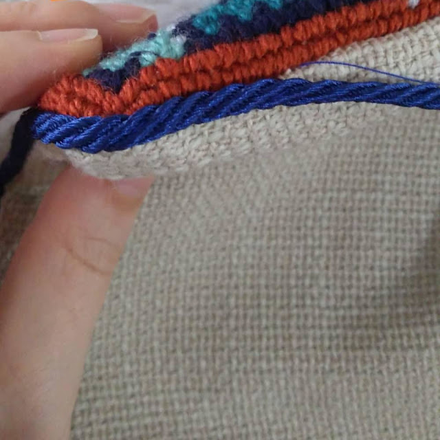 Handstitching the cord edge to a needlepoint cushion with ladder stitch