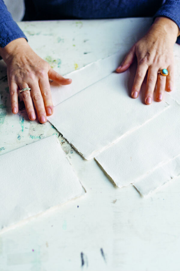 hands folding deckle edge paper sheets - a step in making a Ribbon Bound Book