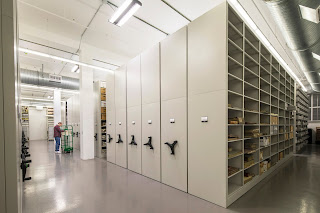The interior of the Alaska State Library and Archives vault, showing tall rolling stacks with ledgers and records boxes.