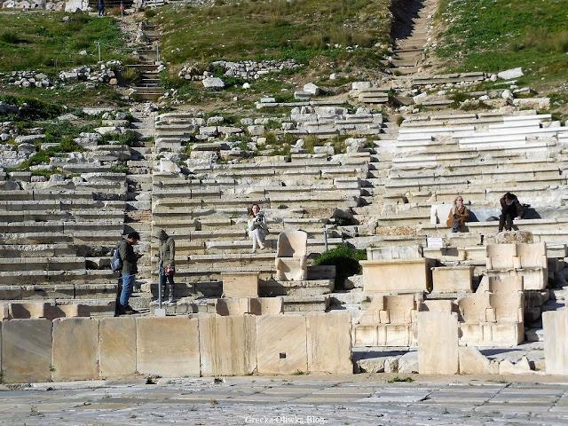 rząd marmurowych zabytkowych siedzeń, turyści, kobieta siedzi na ławce w Teatrze Dionizosa Akropol Ateny