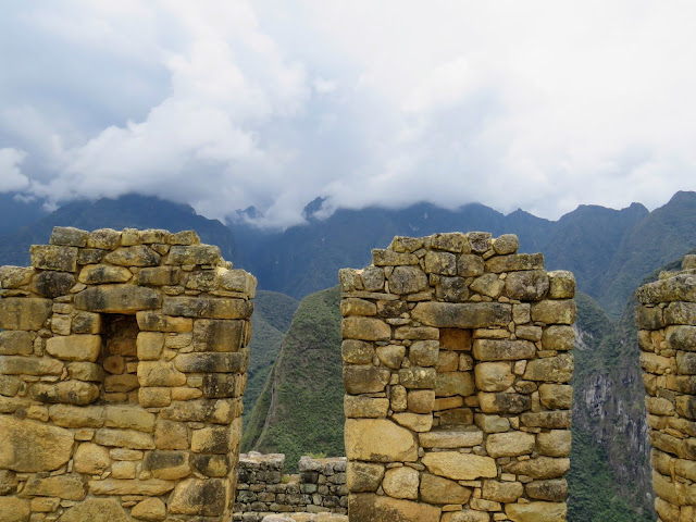 Pictures of Machu Picchu: Trapezoidal niches with low hanging clouds over the Andes at Machu Picchu