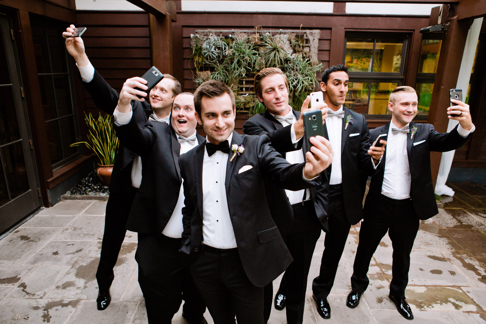 wedding day selfie of the groom and groomsmen taking their own selfies