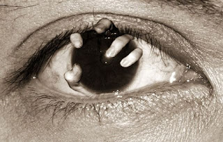 mãos humanas saindo de dentro de olhos humanos