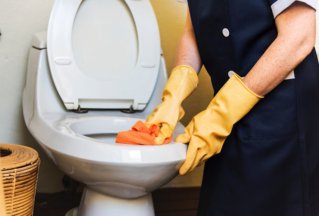 A stock photo of a cleaner cleaning a white toilet wearing yellow rubber gloves