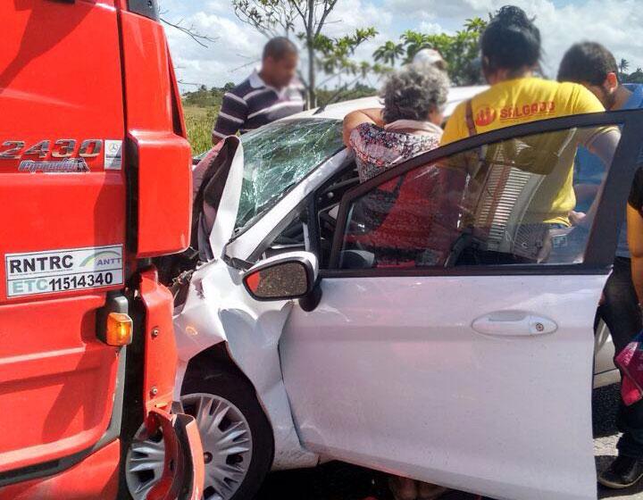 Carro bate de frente com caminhão e jovem fica presa às ferragens