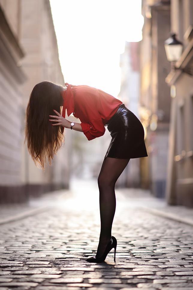 Czerwona koszula, czarna skórzana spódniczka, czarne rajstopy i szpilki