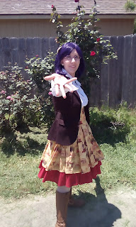 An efeminant looking person with purple hair wearing lolita fashion.  Yellow and red skirt, brown boots and vest, white blouse.  Blowing a kiss to the camera.