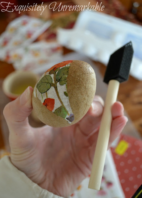 Wearing a coat and holding a half decoupaged paper egg