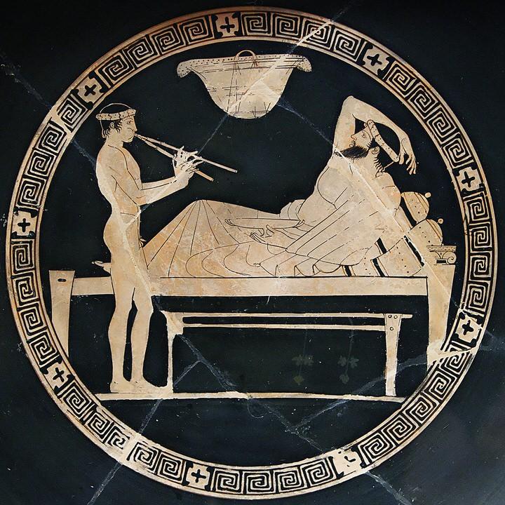 Σκηνή από συμπόσιο: ο άνθρωπος ξαπλώνει σε ένα ανάκλινδρο και ένας νέος παίζει τον αυλό. σκηνή σε αττικό κόκκινο κύπελλο